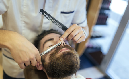 nose close up: Barber cutting beard of a customer