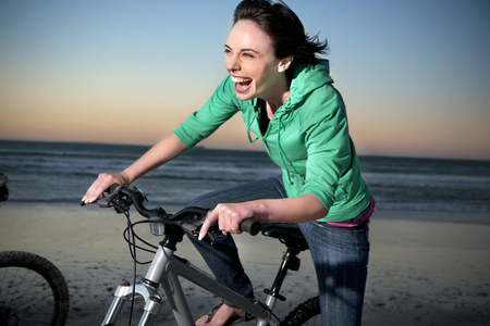 Carefree young woman on mountainbike on the beach