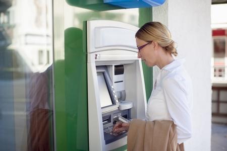 saalfelden: Woman using cash machine LANG_EVOIMAGES