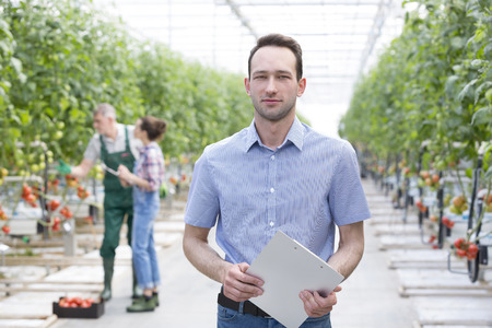 Portrait of man with clipboard in greenhouse