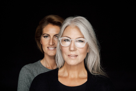 Portrait of mature woman and younger woman standing behind her in front of black background
