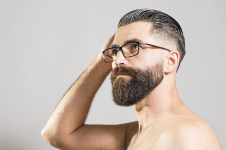 Portrait of a mid adult bare-chested man with full beard and glasses LANG_EVOIMAGES