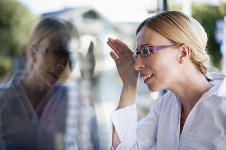 saalfelden: Blond woman looking through window display LANG_EVOIMAGES