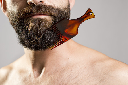 Bare-chested man with comb stuck in beard LANG_EVOIMAGES