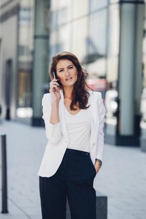 sidewalk talk: Businesswoman outdoors on cell phone