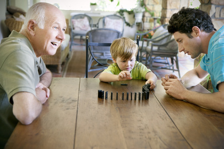 three generations: Little boy playing with his father and grandfather domino