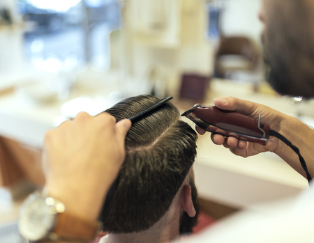 Barber cutting hair of a customer
