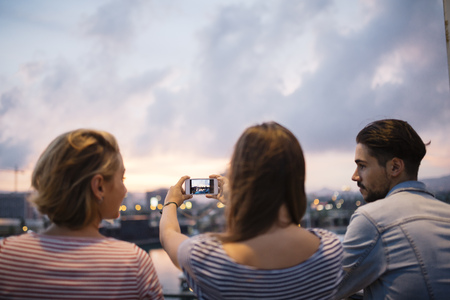 lighted: Spain, Barcelona, back view of three friends taking a picture of view with smartphone
