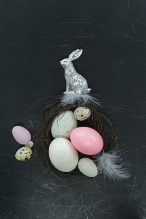 leporidae: Easter nest with easter eggs, silver Easter bunny and feathers LANG_EVOIMAGES