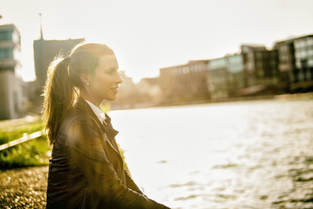 lighted: Germany, Muenster, young woman relaxing at city harbour in evening twilight