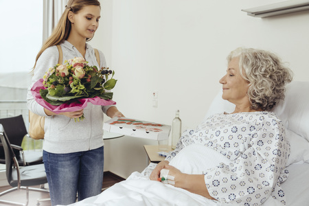 three generations: Granddaughter visiting grandmother in hospital, bringing bunch of flowers LANG_EVOIMAGES