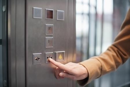 saalfelden: Woman pressing button of a lift LANG_EVOIMAGES