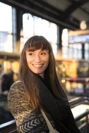 Germany, Berlin, smiling young woman waiting at platform