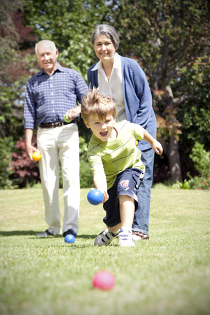 three generations: Little boy playing boccia with his grandparents