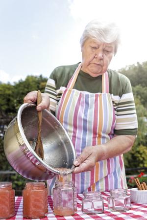 Senior woman pouring homemade applesauce in jam jars