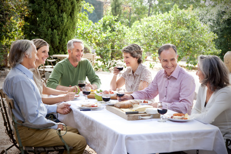 well laid: Spain, Mallorca, six friends sitting at laid table in the garden communicating LANG_EVOIMAGES