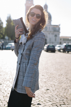 lighted: Italy, Vicenza, smiling brunette woman wearing checkered coat and sunglasses