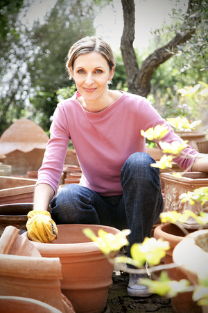Spain, Mallorca, portrait of smiling young woman gardening LANG_EVOIMAGES