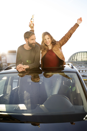 Happy couple with beer bottle looking through sunroof of a car