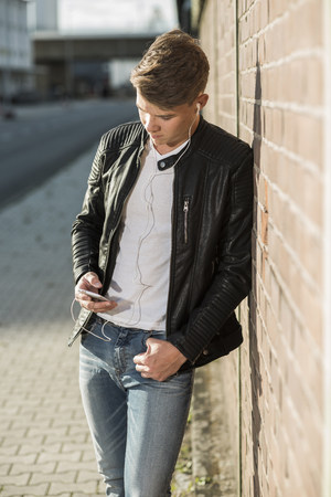 pantalones abajo: Young man wearing earbuds looking at cell phone