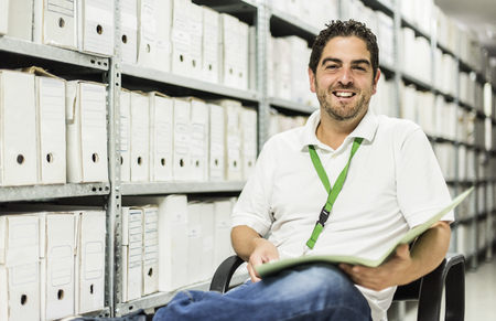 Portrait of smiling man with file sitting in an archive
