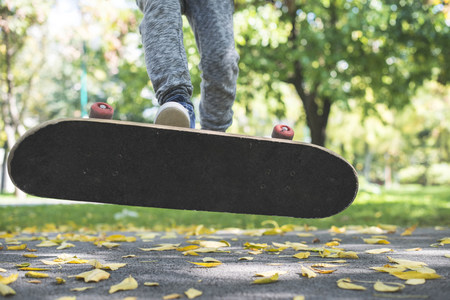 Boy with skateboard in park in autumn LANG_EVOIMAGES