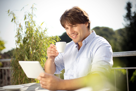 Smiling man with digital tablet and cup of coffee on balcony
