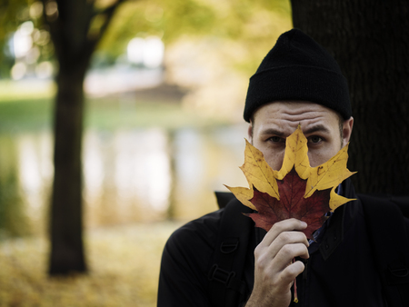 Portrait of man wearing woolly hat hiding behind autumn leaves LANG_EVOIMAGES