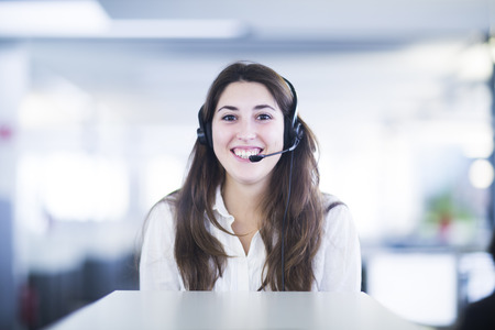 Portrait of smiling young woman with headset in an office LANG_EVOIMAGES