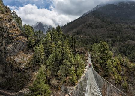 Nepal, Himalaya, Khumbu, trekker on footbridge in the mountains