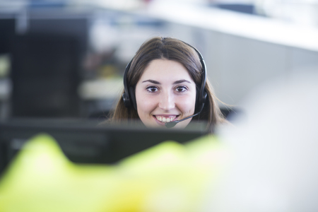 Portrait of smiling young woman with headset at her workplace