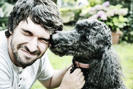 Poodle licking the face of his owner in the garden LANG_EVOIMAGES