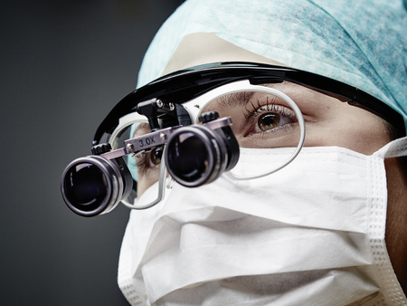 Portrait of young doctor wearing mask and magnifying spectacles LANG_EVOIMAGES