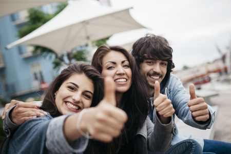 Italy, Rimini, portrait of three happy friends outdoors with thumbs up LANG_EVOIMAGES