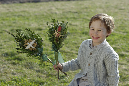 religious clothing: Germany, Upper Bavaria, Portrait of smiling little boy with Palmbusch on a meadow