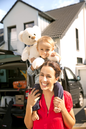 Mother carrying son with teddy bear on shoulders, standing in front of home