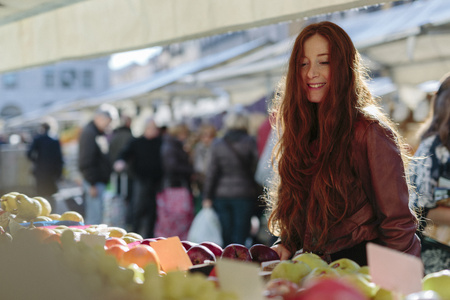 trade off: Smiling woman at fruit market