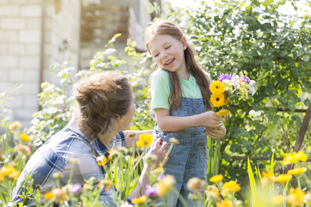 Mother and daughter picking flowers in field LANG_EVOIMAGES