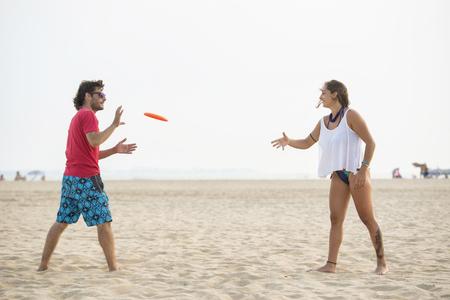 Spain, Cadiz, El Puerto de Santa Maria, Couple playing frisbee on the beach