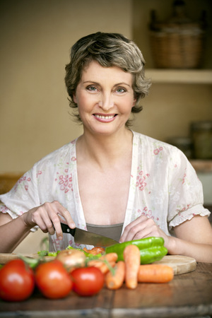 Portrait of smiling woman chopping vegetables LANG_EVOIMAGES