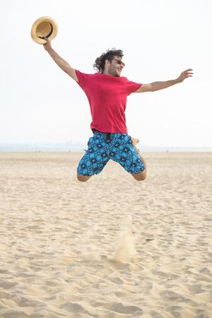sun energy: Spain, Cadiz, El Puerto de Santa Maria, Man jumping on the beach