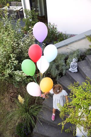 bajando escaleras: Chica caminando por las escaleras con coloridos globos