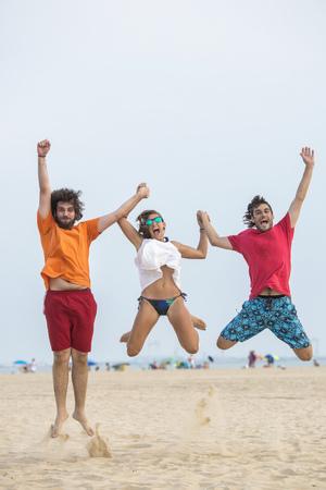ardor: Spain, Cadiz, El Puerto de Santa Maria, Friends jumping on the beach
