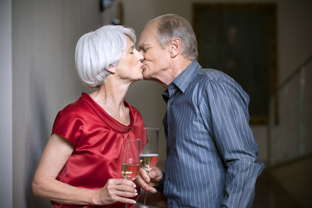 africa kiss: Senior couple kissing and clinking glasses