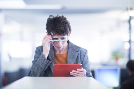 Woman with reading glasses using digital tablet in an office