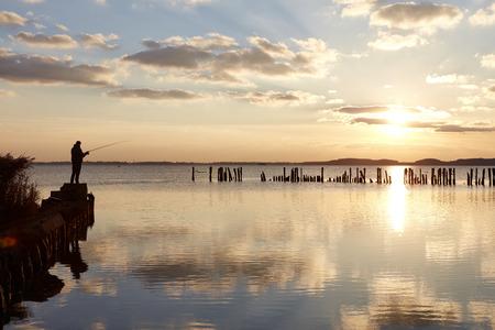 mecklenburg western pomerania: Germany, Mecklenburg-Western Pomerania, Ruegen Island, Glowe, Angler on Spyckerscher See at sunset LANG_EVOIMAGES
