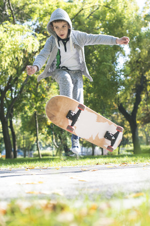 Boy doing a skateboard trick in park in autumn