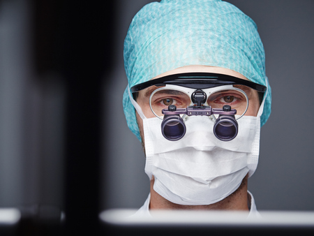 obscuring: Portrait of young doctor wearing mask and magnifying spectacles LANG_EVOIMAGES