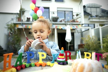 Happy toddler celebrating birthday in garden LANG_EVOIMAGES
