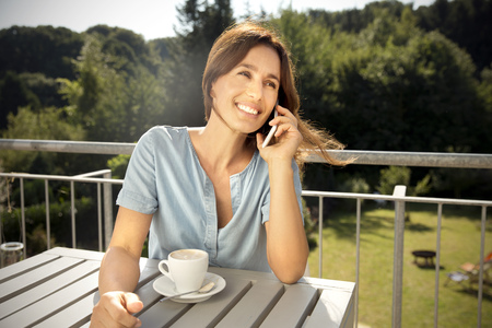 Woman on balcony with cup of coffee on the phone LANG_EVOIMAGES